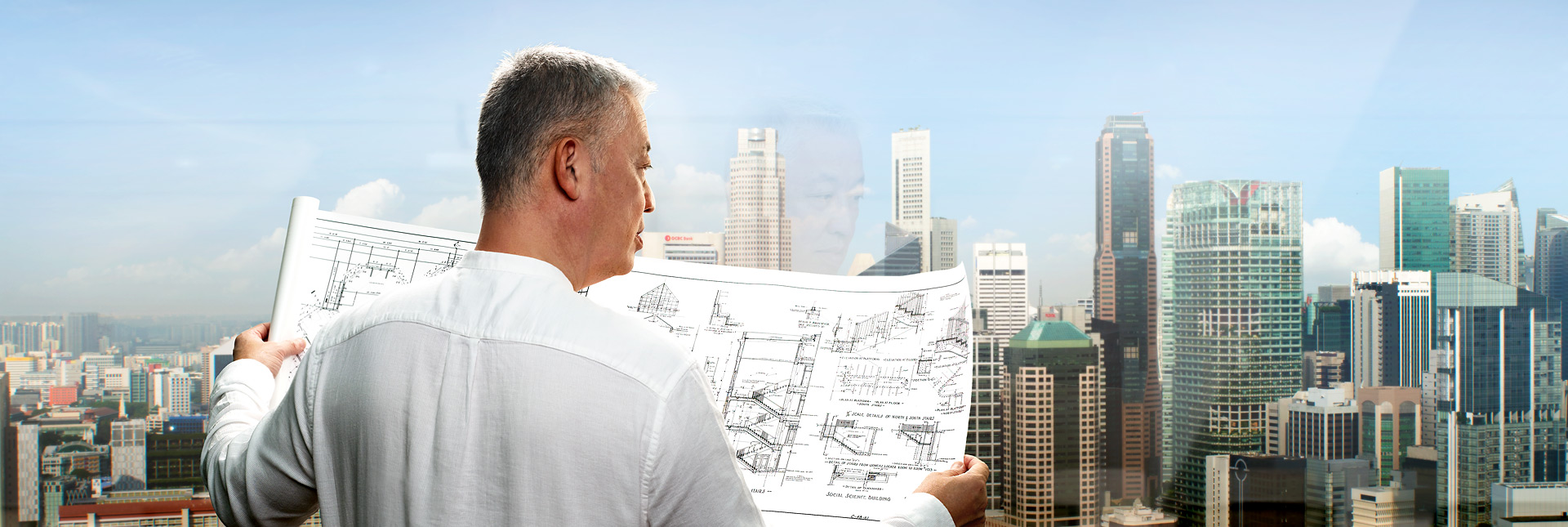 Man looking at blueprints by window
